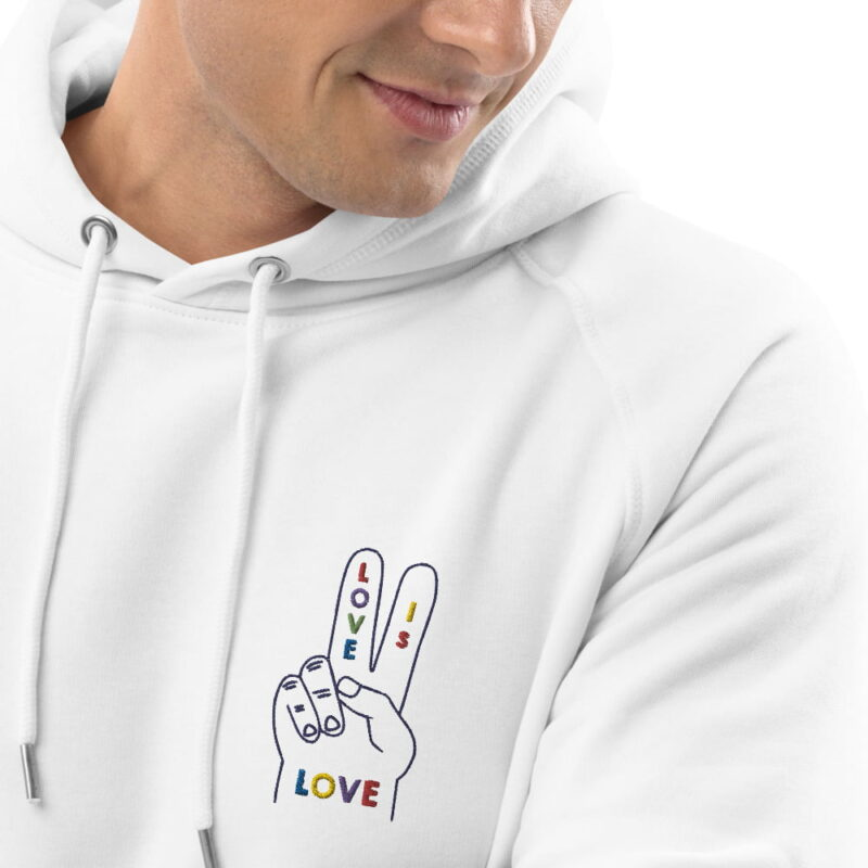"""Hoodie with a peace and love design embroidered on the chest. The message """"Love is love"""" is written in rainbow colors on a hand making the peace sign. Hoodies - LGBTQ+ Gay Pride Apparel - unisex eco hoodie white zoomed in 3 607dfe9b3bef1"""