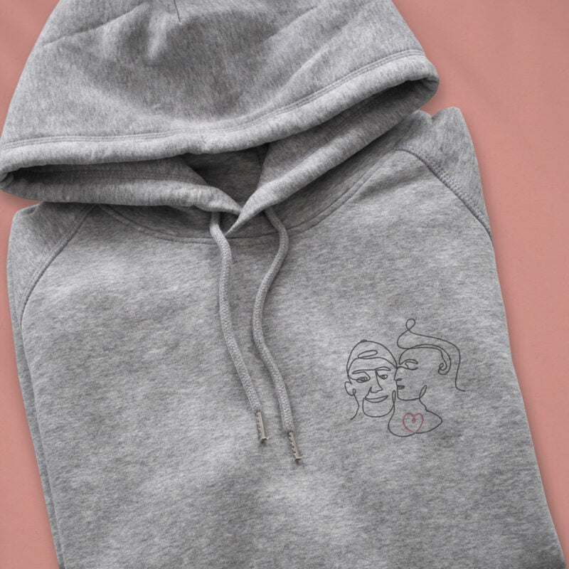 Hoodie with an embroidery of 2 men in love. One guy is kissing the cheek of the other one. The drawing represents 2 lovers with a single pencil stroke. A red heart connect the men. Hoodies - LGBTQ+ Gay Pride Apparel - lovers color hoodie 2