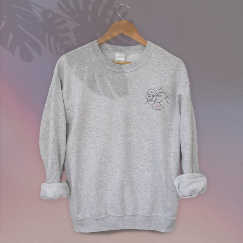 Relax fit sweat with an embroidery on the chest showing 2 lovers. One guy is kissing the cheek of the second man. Sweats - LGBTQ+ Gay Pride Apparel - lovers relax 1