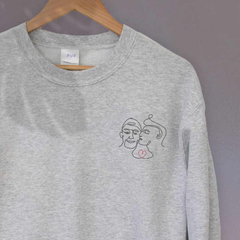 Relax fit sweat with an embroidery on the chest showing 2 lovers. One guy is kissing the cheek of the second man. Sweats - LGBTQ+ Gay Pride Apparel - lovers relax 2