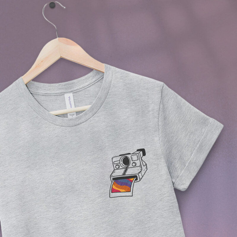 T-shirt with an embroidery on the left chest. This embroidery represents a vintage camera. A rainbow photo comes out of the Polaroid. T-shirts - LGBTQ+ Gay Pride Apparel - pola tshirt 1